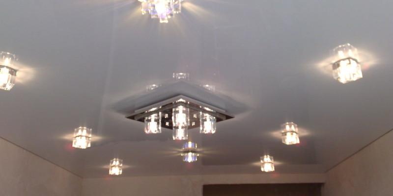 Глянцевый белый потолок в зале, фото со светильниками