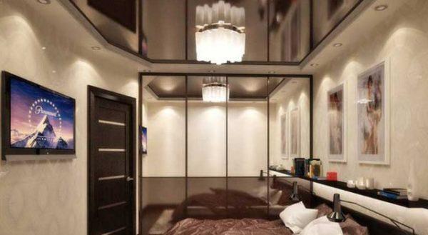 Глянцевый потолок шоколадного цвета визуально увеличивает спальню