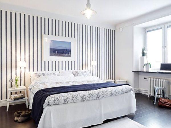 Обои в полоску подчеркивают сдержанное оформление интерьера спальни