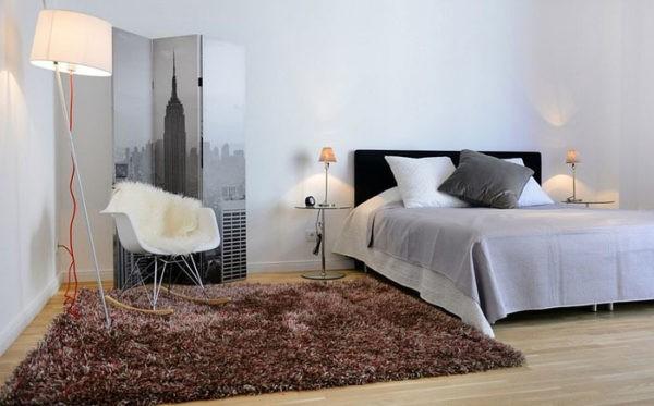 Мягкий коврик из искусственного меха гармонично смотрится возле кровати