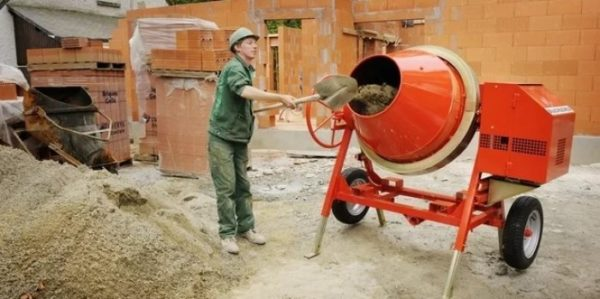 Сыпучие компоненты строители забрасывают в бетономешалку лопатой