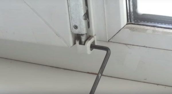 Горизонтальный винт на нижней петле окна