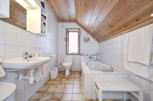 Скромный белый кафель идеально смотрится в сочетании с деревянным потолкомСкромный белый кафель идеально смотрится в сочетании с деревянным потолком