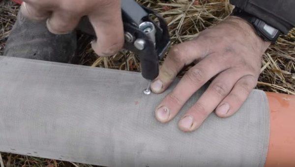 Фиксация сетки на трубе осуществляется заклепками
