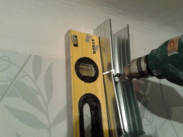 Процесс установки профиля на стену. Если перекрытие имеет кривизну, то направляющую подрезают